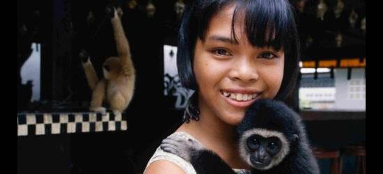 Chica joven y mono del animal doméstico, Phuket